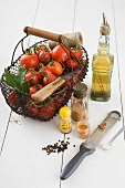 Fresh tomatoes in a wire basket, olive oil and spices