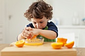 A little boy pressing oranges