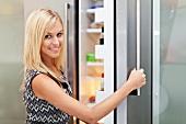 A woman opening a fridge