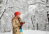 A woman drinking coffee in a winter landscape