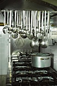 Kitchen utensils above a cooker in a commercial kitchen