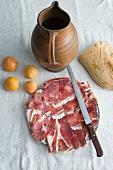 Sliced Prosciutto, plum tomatoes, white bread and a terracotta jug