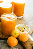 Jars of apricot jam and fresh apricots
