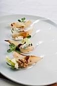 Spoon canapés with sautéed pears and blue cheese