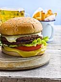Cheeseburger mit Pommes frites und Bierglas