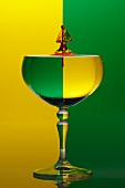 A wine glass with water drops against a green and yellow background