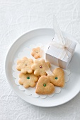 Heart and flower-shaped biscuits decorated with sugar pearls and a small gift on a plate