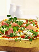 Unleavened bread topped with pesto, ham and cress