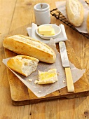 A mini baguette and butter on a wooden board