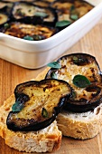 Slices of baguette topped with marinated aubergine slices