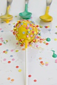 A yellow cake pop decorated with colourful sugar sprinkles