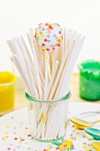 A white cake pop and lots of lolly sticks in a glass