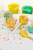 Cake pops decorated with colourful sugar sprinkles and icing sugar on spoons