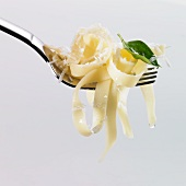 Tagliatelle, oil, basil and grated Parmesan on a fork