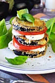 A tower of fried aubergine slices, tomato and mozzarella