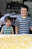 Two young boys in front of a table of freshly made raw pasta