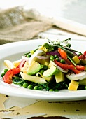 Pasta and vegetable salad with avocado, spinach, peas and cheese