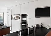 A white fitted kitchen with a black work surface