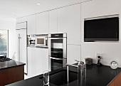 Eine Einbauküche in Weiss mit schwarzer Arbeitsfläche