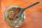 Dried herbs and flowers in a jar with a wooden scoop