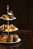 Various types of breakfast pastries and muffins on a cake stand