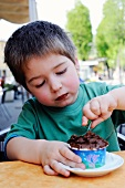 A little boy eating chocolate ice cream in an ice cream cafe