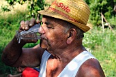 An older man in a straw hat drinking a glass of white wine
