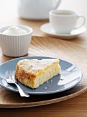 Slice of almond and lemon cake with cream and a cup of tea
