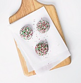 Three Vanilla Cookies with Christmas Colored Sprinkles; On Parchment on Cutting Board