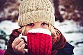 Kleines Mädchen trinkt eine Tasse Tee im Winter