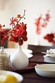 Blumenvasen auf gedecktem Tisch