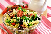 A bowl of pasta salad with green beans, peas, tomatoes, olives and spring onions