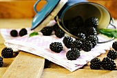 A tin full of blackberries spilling onto a table