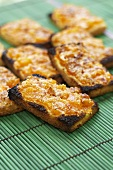Slices of toast topped with apricots and Parmesan cheese