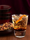 Kahlua and Vodka Drink on Ice with Orange Peel; Bowl of Mixed Nuts