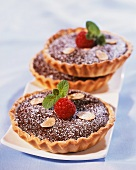 Cocoa tartlets topped with almonds and raspberries