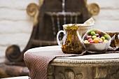 Karaffe aus Glas mit gesprenkeltem Muster neben Obstschale aus Metall auf rustikal antikem Steintisch