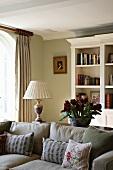 Traditionelles Wohnzimmer mit grauem Polstersofa vor weiss lackiertem Regalschrank in antikem Stil