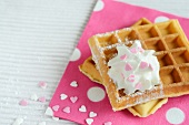 Waffles with cream and sugar hearts on a pink napkin