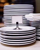 Stacks of Plain White Plates; White Linen Napkins and a Blank Place Card