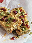 Whole Grain Bread Topped with Peanut Butter, Pumpkin Seeds and Dried Cranberries