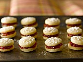 Strawberry Jam Filled Shortbread Cookies Dusted with Powdered Sugar on a Sheet Pan