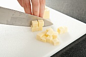 Hands Cutting Cheddar Cheese Into Cubes