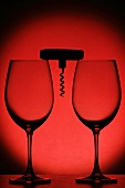 Two empty wine glasses and a corkscrew against a red background