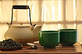 Green tea leaves, a teapot and teacups