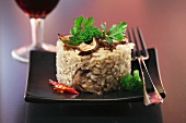 Porcini mushroom risotto with a glass of red wine in the background