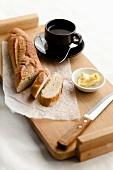 Angeschnittenes Baguettebrot auf Tablett mit Butter & Tasse Kaffee