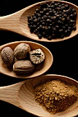 Three Wooden Spoons Full of Spices; Peppercorns, Nutmeg and Cinnamon