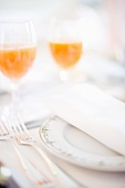 A place setting with a napkin and glasses of juice