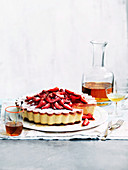 A cheesecake with strawberries and ginger syrup